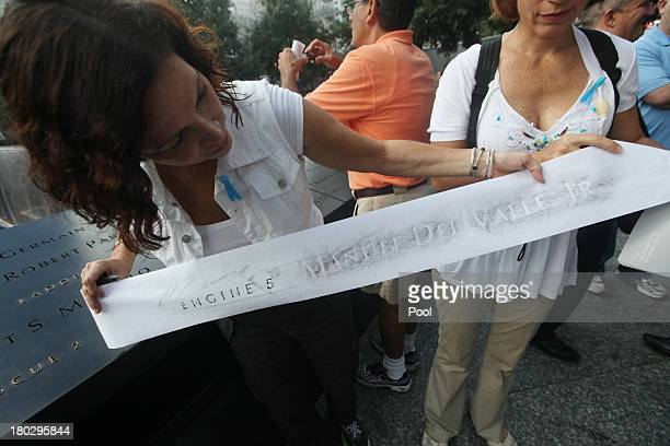 Judy DelValle stepmother of firefighter Manuel DelValle holds an etching of her stepson at the 9/11 Memorial during ceremonies for the twelfth...