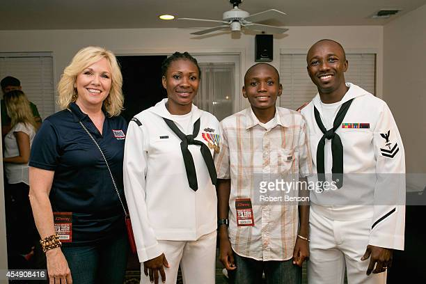 Judy Forrester President and CEO at USO San Diego stands alongside a military USO family Marie Esther Kiendrebeogo Oswald Kiendrebeogo and Roland...