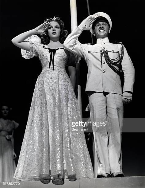 Judy Garland and Mickey Rooney stand at attention while the Stars and Stripes are raised during the stirring finale of MGM's 'Strike Up the Band'...