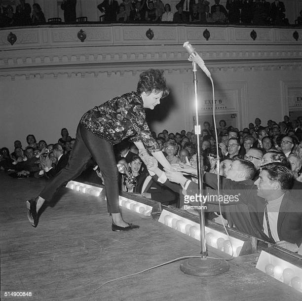 Judy Garland leans over the footlights to greet some of her enthusiastic fans during her concert at Carnegie Hall Judy thrilled a standingroomonly...