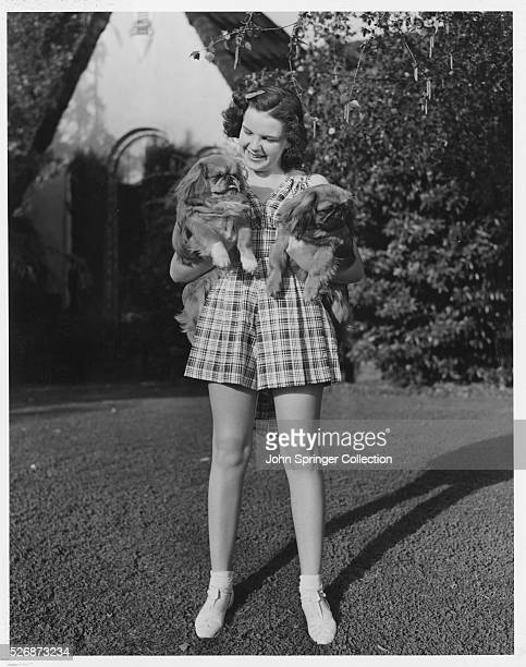 Judy Garland takes time off from her singing acting and dancing roles to enjoy her dogs at home