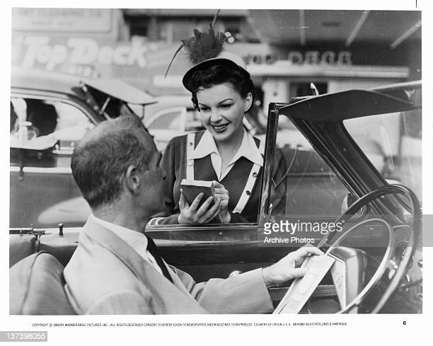 Judy Garland taking food order from man in car in a scene from the film 'A Star Is Born', 1954.