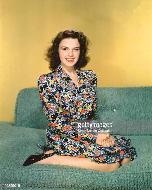 Judy Garland US actress and singer weaing a floral print dress kneeling on a green sofa in a studio portrait against a yellow background circa 1945