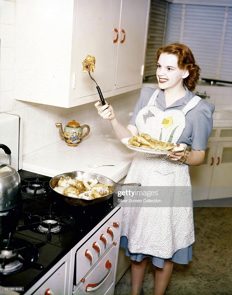 Judy Garland (1922-1969), US singer and actress, wearing a cooking apron to fry pieces of chicken in a frying pan on a gas hob in a kitchen, circa 1955.
