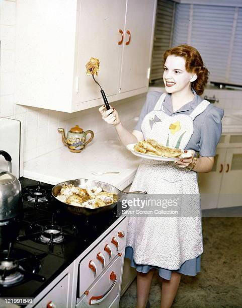 Judy Garland US singer and actress wearing a cooking apron to fry pieces of chicken in a frying pan on a gas hob in a kitchen circa 1955
