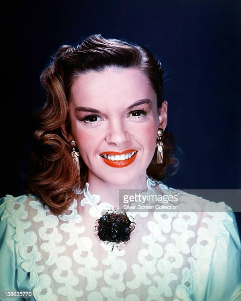 Judy Garland US singer and actress wearing a white lace blouse with and gold drop earrings in a studio portrait circa 1950