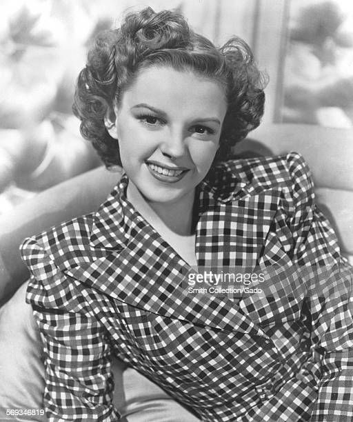 Judy Garland wearing a checkered shirt lounging on a chair 1950