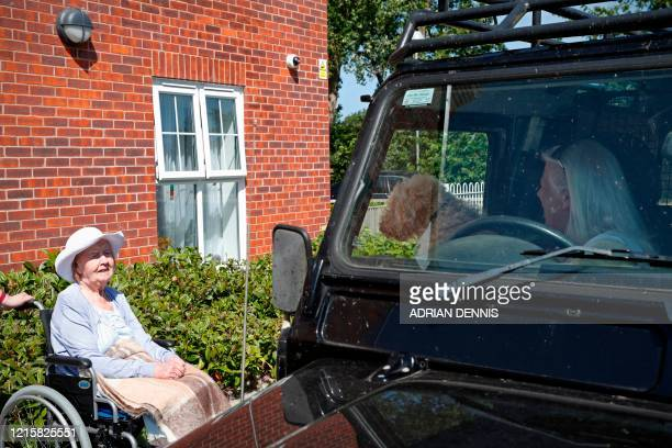 "Judy Gillingham shows her dog ""Hector Weasel"" to her friend Dorothy Saxby during a drive-through visit at Gracewell, a residential care home in..."