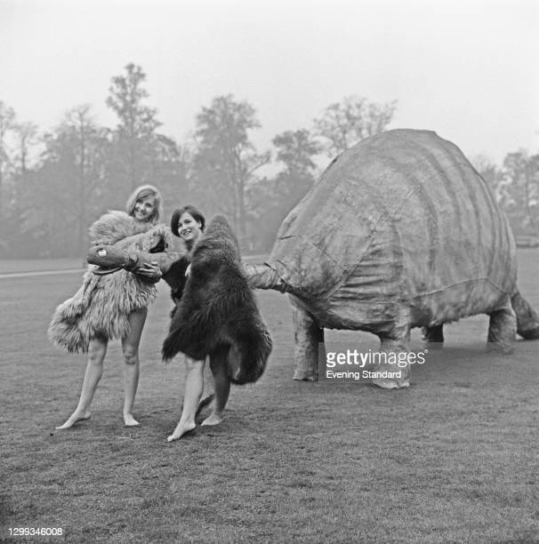 Judy Harding and Jane Dalgleish attend the Cambridge University Rag in prehistoric costumes with a 'dinosaur', UK, 18th November 1966.