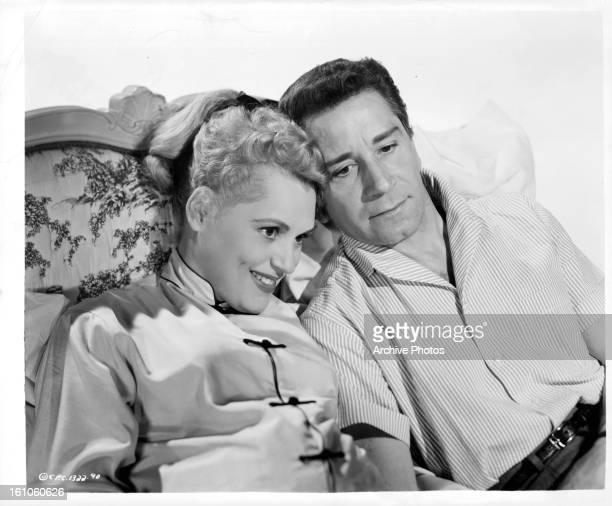 Judy Holliday and Richard Conte sitting on couch together in a scene from the film 'Full of Life' 1956