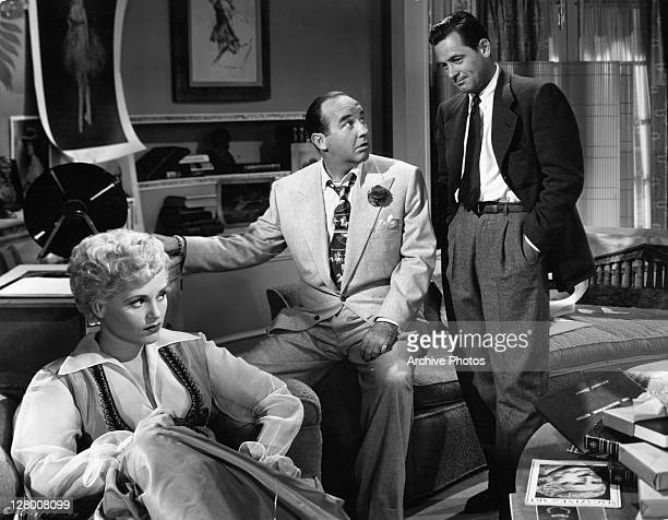 Judy Holliday Broderick Crawford William Holden sitting and holding his shoe while J stands behind him in a scene from the film 'Born Yesterday' 1950