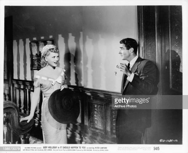 Judy Holliday holding hat talks with Peter Lawford who is dangling keys at her in a scene from the film 'It Should Happen To You' 1954