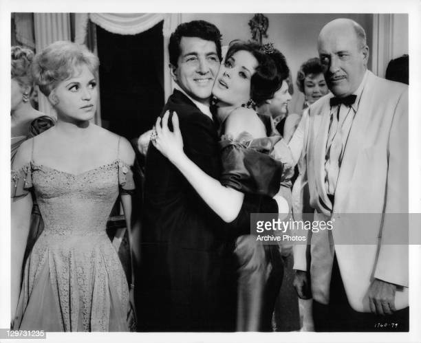 Judy Holliday looks on while Dean Martin gives Nancy Walters a big hug in a scene from the film 'Bells Are Ringing' 1960