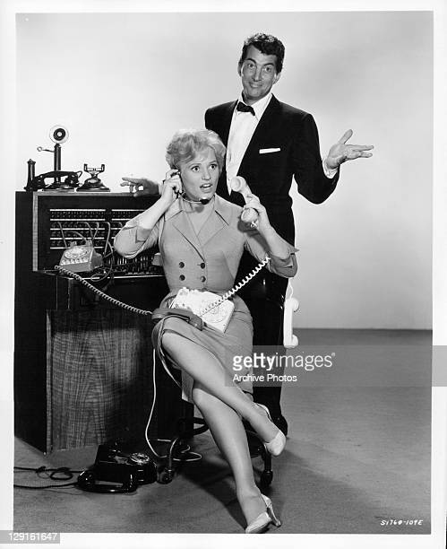 Judy Holliday manning the phones with Dean Martin behind her in a scene from the film 'Bells Are Ringing' 1960