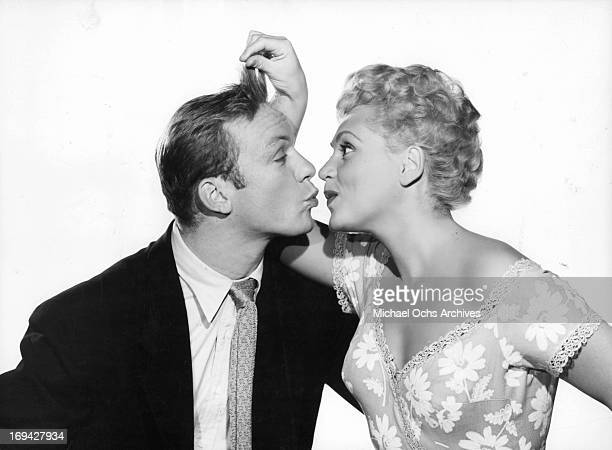 Judy Holliday plays with Aldo Ray's hair in publicity portrait for the film 'The Marrying Kind' 1952