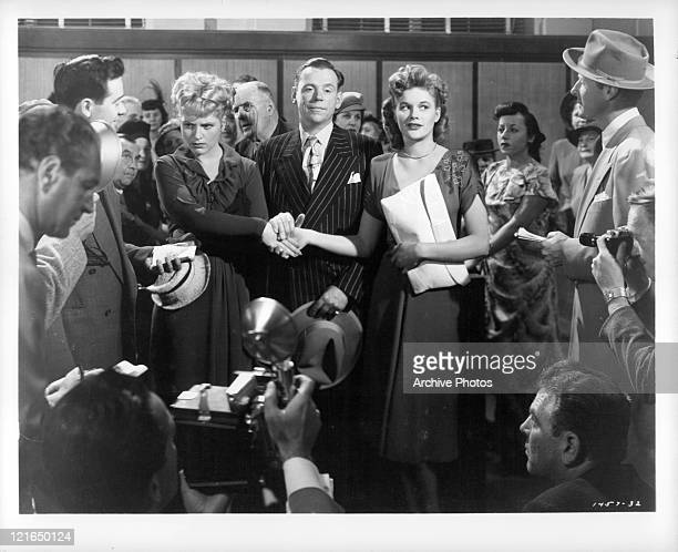 Judy Holliday Tom Ewell and Jean Hagen shake hands in front of a group of reporters in a scene from the film 'Adam's Rib' 1949