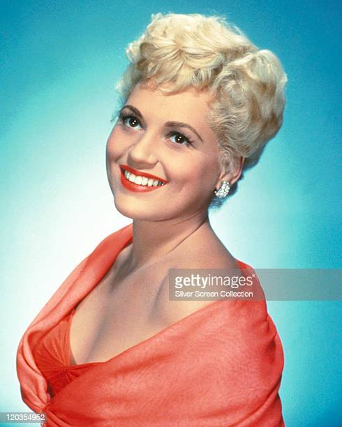 Judy Holliday US actress smiling wearing a red outfit in a studio portrait against a bluw background circa 1950