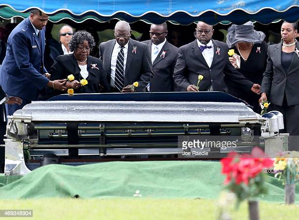 Judy Scott and Walter Scott Sr are joined by others as they prepare to place flowers on the coffin of their son Walter Scott during the burial...