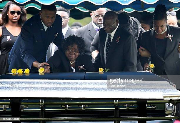 Judy Scott lays a flower on the casket of her son Walter Scott as her husband and Walter's father Walter Scott Sr helps her during the burial at the...