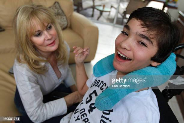 Judy Susser left of Boca Raton Florida is pictured December 6 with her disabled son Adam who has received stemcell treatments Adam was born with...