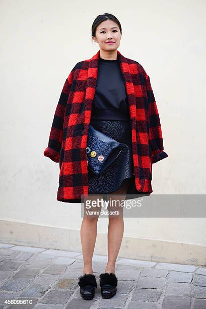 Judy Wong poses wearing a Balmain coat MSGM skirt House of Holland bag and Acne shoes on September 25 2014 in Paris France