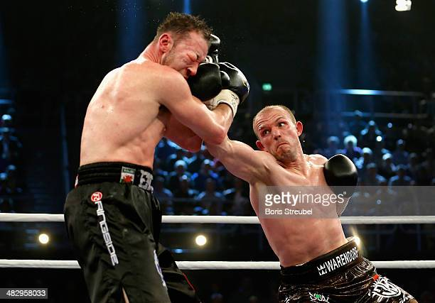 Juergen Braehmer of Germany exchanges punches with Enzo Maccarinelli of Wales during their WBA light heavyweight title fight at Stadthalle Rostock on...