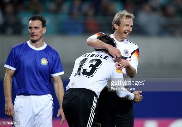 Juergen Klinsmann and Karlheinz Riedle of the World Champion 1990 celebrate their teams first goal next to Andreas Wagenhaus of the DFV Legend during...