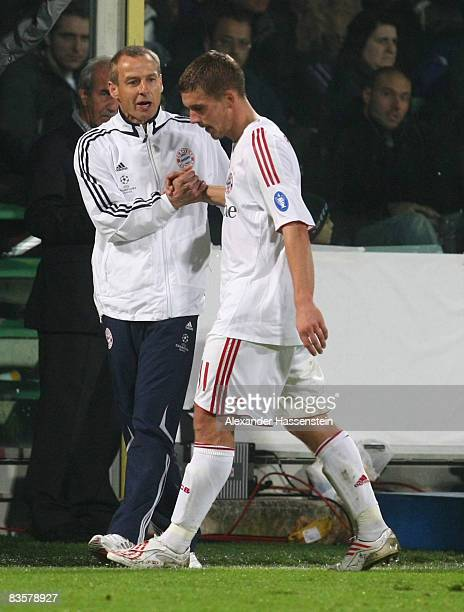 Juergen Klinsmann head coach of Bayern Muenchen shake hands with his player Lukas Podolski after his substitution during the UEFA Champions League...