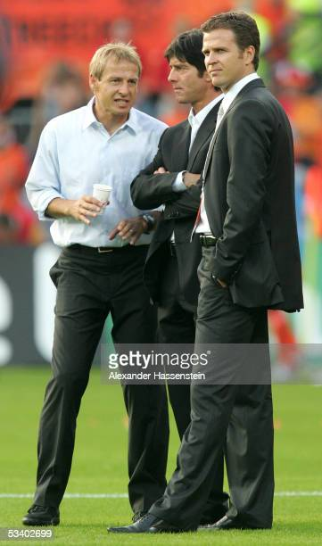 Juergen Klinsmann head coach of Germany talks with his assistent Joachim Loew and Team Manager Oliver Bierhof before the international friendly match...