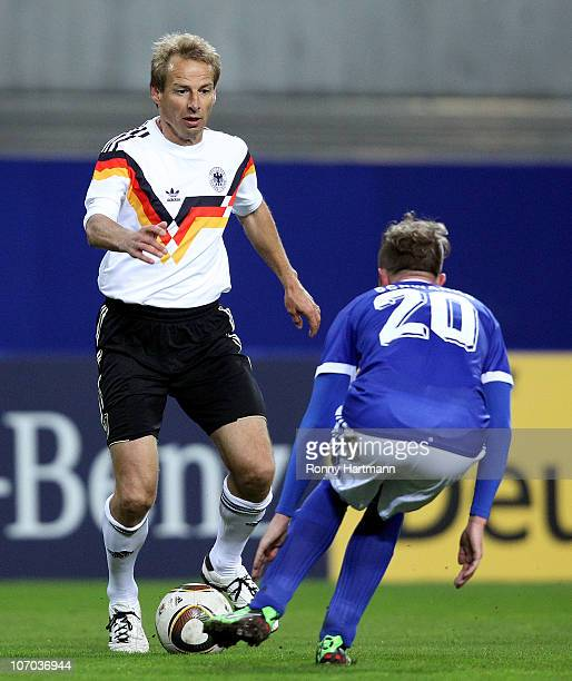 Juergen Klinsmann of the World Champion 1990 battles for the ball with Joerg Schwanke of the DFV Legend during the Reunification match between the...