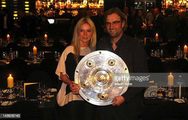 Juergen Klopp head coach of Dortmund poses with his wife Ulla with the trophy at View restaurant on May 5 2012 in Dortmund Germany