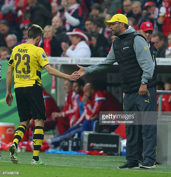 Juergen Klopp head coach of Dortmund taps hands with Kevin Kampl of Dortmund after he had been sent off haveing been given the red card by referee...
