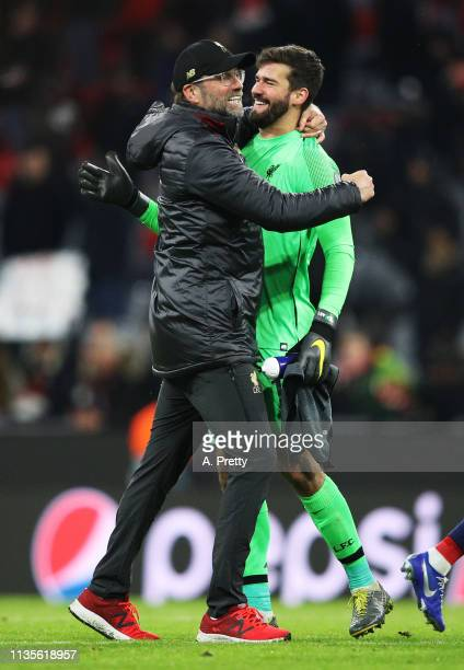 Juergen Klopp head coach of Liverpool congratulates Alisson Becker of Liverpool after the UEFA Champions League Round of 16 Second Leg match between...