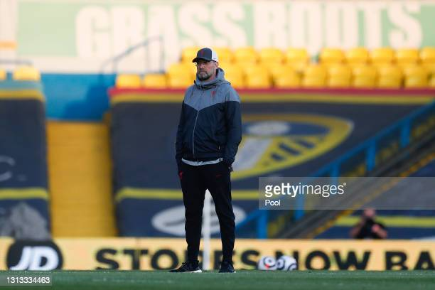 """Juergen Klopp, Manager of Liverpool looks on as a sign reading """"Grassroots"""" is seen in the background prior to the Premier League match between Leeds..."""