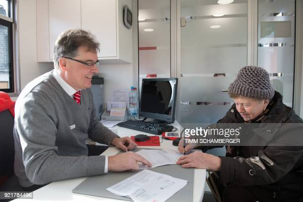 Juergen Schaller employee of the savings bank Sparkasse serves a customer in a mobile office bus in Tschirn southern Germany on January 30 2018 Bank...