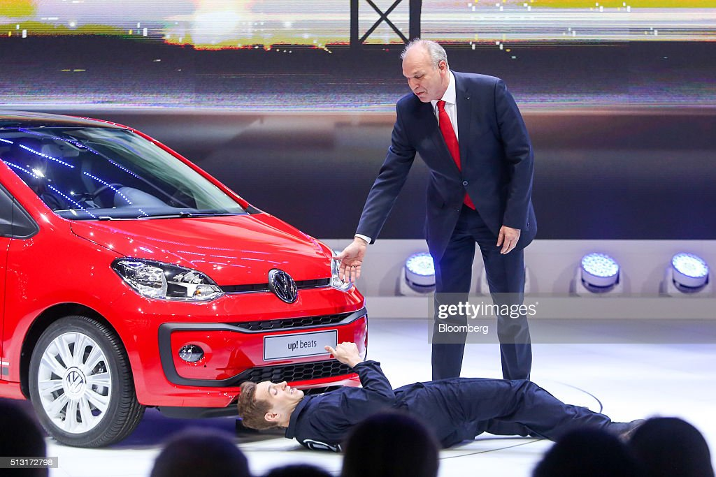 Juergen Stackman, sales chief of Volkswagen AG, offers a hand to Simon Brodkin, comedian, during a protest at a news conference on the first day of the 86th Geneva International Motor Show in Geneva, Switzerland on Tuesday, Mar. 1, 2016. The show opens to the public on Mar. 3, and will showcase the latest models from the world's top automakers. Photographer: Chris Ratcliffe/Bloomberg via Getty Images