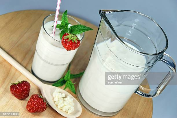 Jug and glass of kefir, decorated with fresh strawberries