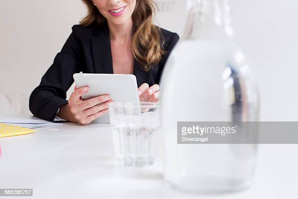 Jug and glass of water with mature woman using digital tablet