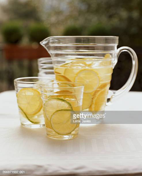 Jug and glass of white sangria on table, close-up