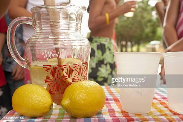Jug, lemons and cups on lemonade stall, children (5-13) in background
