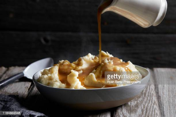 jug of gravy being poured onto bowl of steaming mashed potatoes, studio shot - food staple stock pictures, royalty-free photos & images