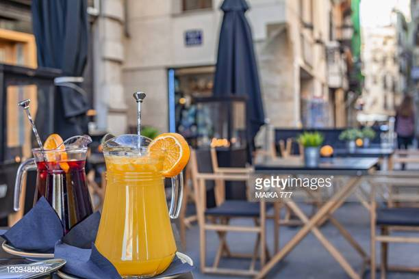 a jug of orange juice and other of sangria on the table in an outdoor restaurant in valencia, spain - valencia spain stock pictures, royalty-free photos & images