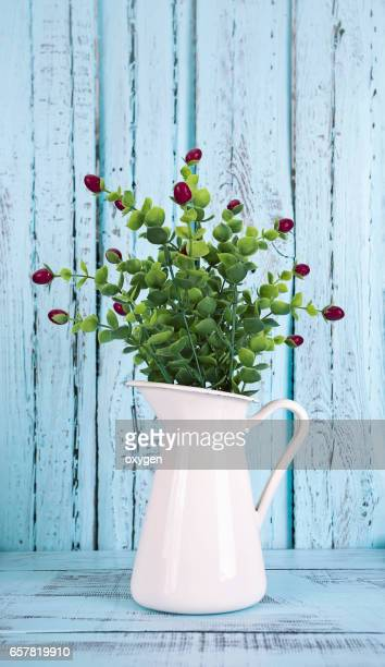 Jug with flowers on blue wooden background