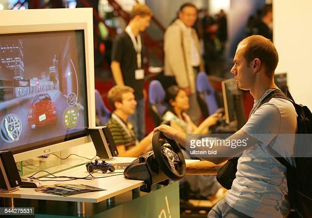 Jugendliche Besucher der Games Convention Messe in Leipzig spielen an einer Spielkonsole von Logitech