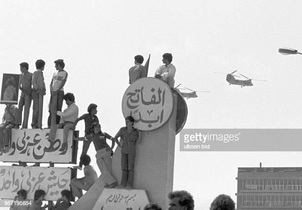 Jugendliche haben erhöhte Standpunkte erklommen und verfolgen eine Militärparade der libyschen Streitkräfte in Bengasi im September 1979 anlässlich...