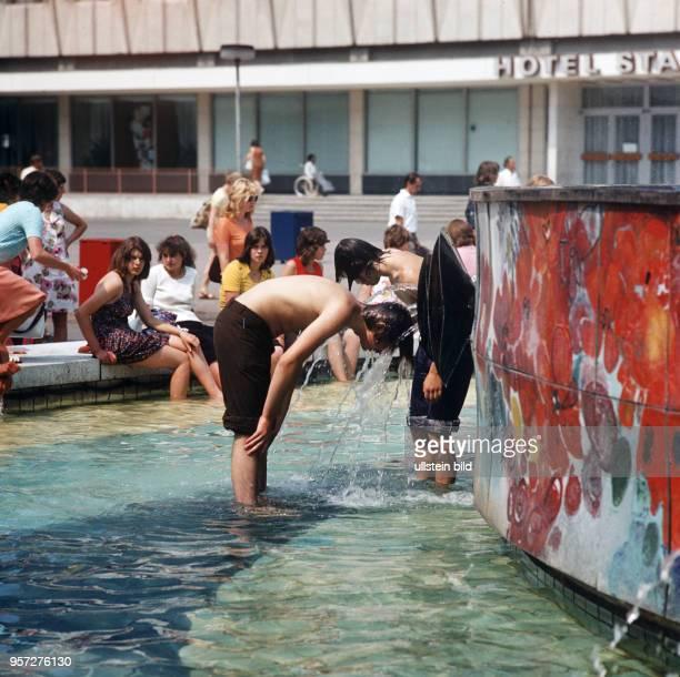 """Jugendliche kühlen ihre Köpfe im Wasser im """"Brunnen der Völkerfreundschaft"""" auf dem Alex in Berlin, aufgenommen am . Im Volksmund wurde der Brunnen..."""