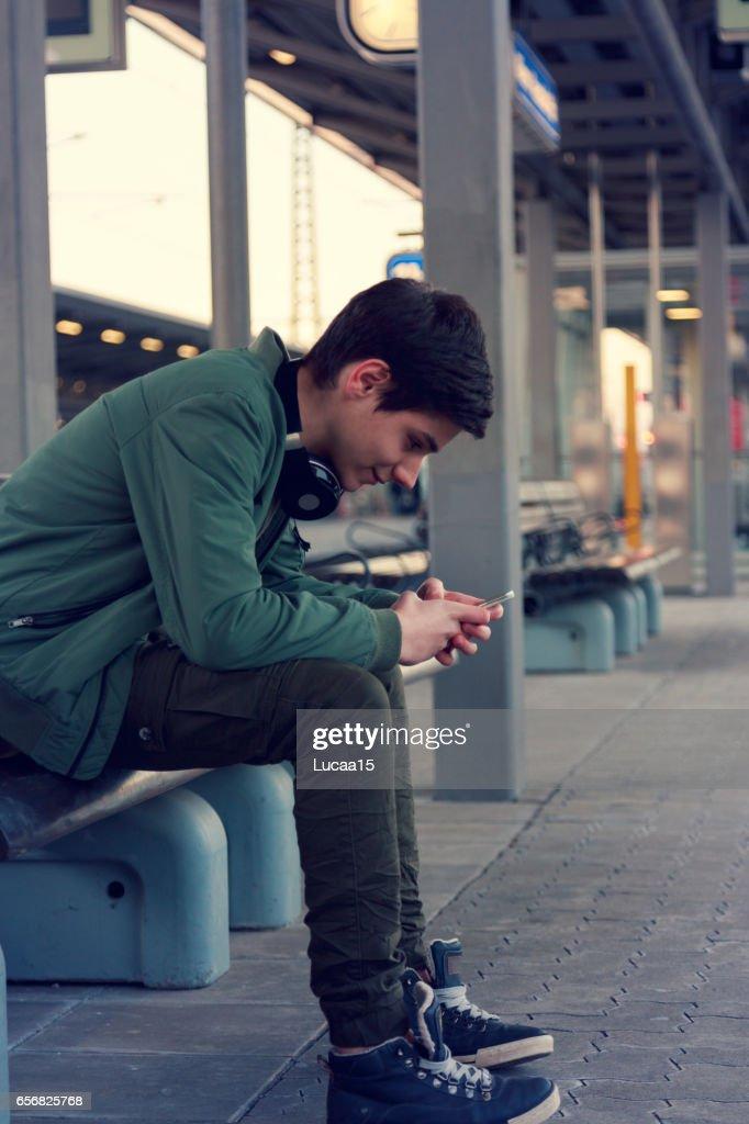 Jugendlicher hört ムジーク und wartet auf dem ツーク : ストックフォト