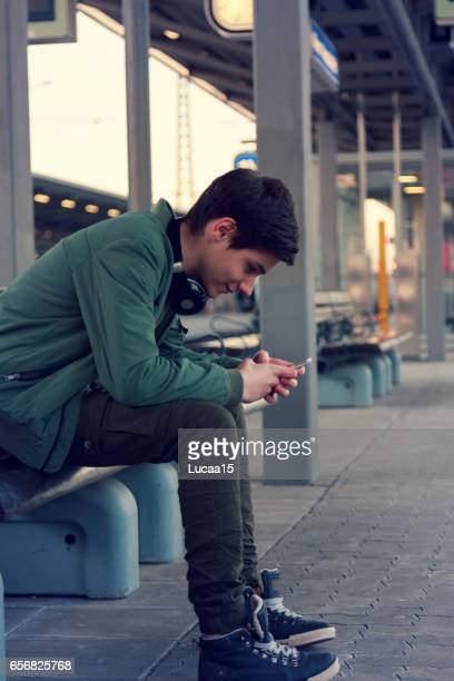 jugendlicher hört musik und wartet auf dem zug - zuhören foto e immagini stock