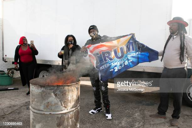 Jugganaut MC burns a Trump flag during a watch party of the televised Presidential Inauguration ceremony at Tree House Lounge on January 20, 2021 in...