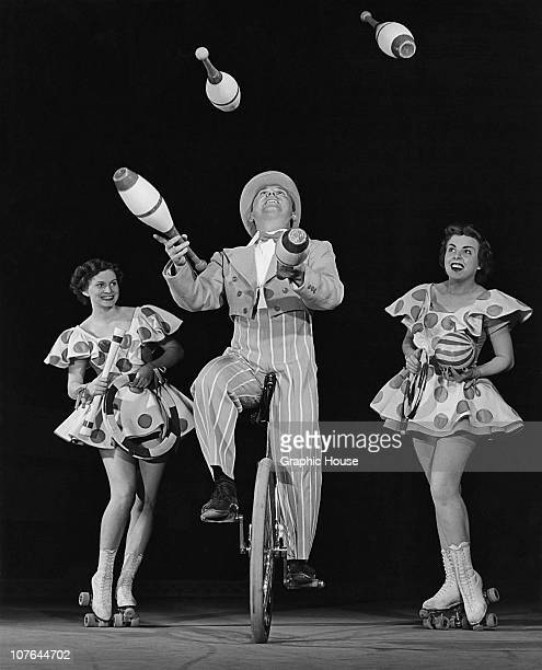 Juggler Boy Foy performing on a unicycle with a set of clubs as two rollerskating female assistants look on during a 'Vanities' show 1953